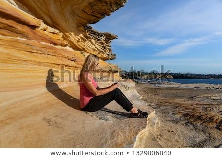 Woman sitting under sandstone rock ledge by the ocean Stock photo © lovleah