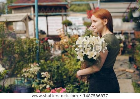 Mosolyog gyönyörű vörös hajú nő lány tart liliomok Stock fotó © pressmaster