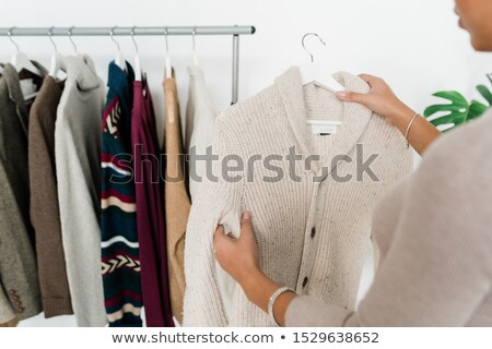 Casual white knitted cardigan on hanger held by young shopaholic Stock photo © pressmaster