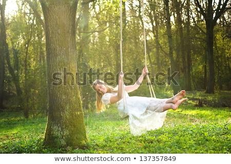 Młoda kobieta huśtawka kwiat ogród dziewczyna drzewo wiosną Zdjęcia stock © galitskaya