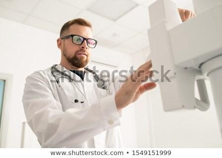 Bebaarde jonge arts permanente tijdgenoot medische apparatuur Stockfoto © pressmaster
