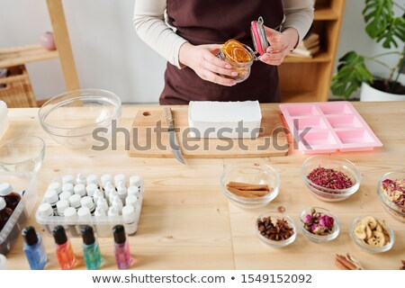 Girl opening small jar with dry orange slices to put them into liquid soap mass Stock photo © pressmaster