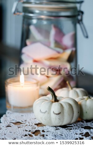 baby boo pumpkin, lighted candle and a glass jar with white pink sweets marshmallow Stock photo © laciatek