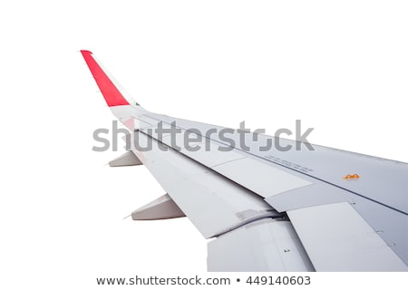 Airplane wing above fluffy white clouds in a blue sky. Stock photo © artjazz