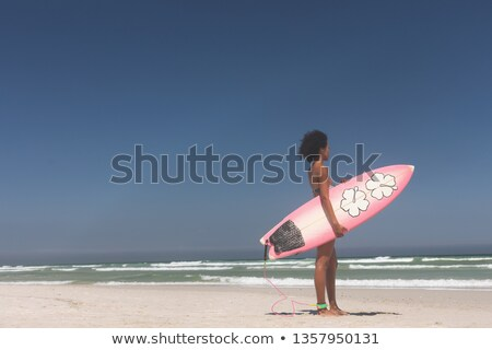 Side view of fit Mixed-race female surfer with a surfboard standing on a beach on a sunny day Stock photo © wavebreak_media