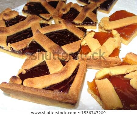 Fresh baked tarts with marmalade or apricot jam filling on white Stock photo © marylooo