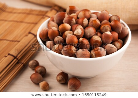 whole hazelnut kernels in a glass bowl and on a table still life Stock photo © mizar_21984