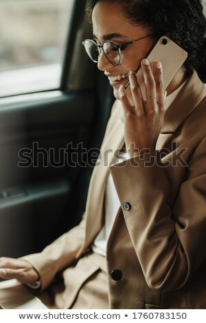 Young woman with her cell phone sitting in the backseat of a car Stock photo © lightpoet