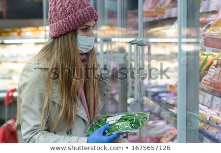 Woman in full corona outfit shopping in supermarket Stock photo © Kzenon