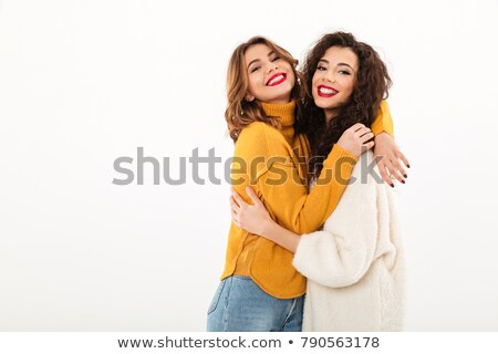 Portrait of two pleased women looking at camera and hugging Stock photo © deandrobot