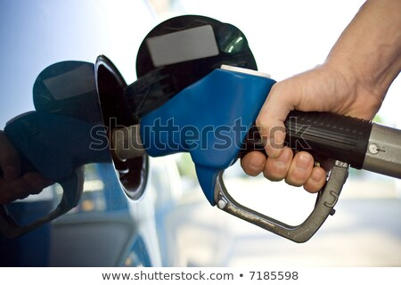 close up image of a mens hand refilling the car with a gas pump stock photo © zurijeta