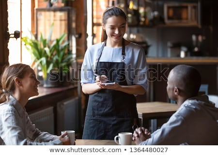 a man and a woman ordering at the restaurant, a waitress is writing the order Stock photo © photography33