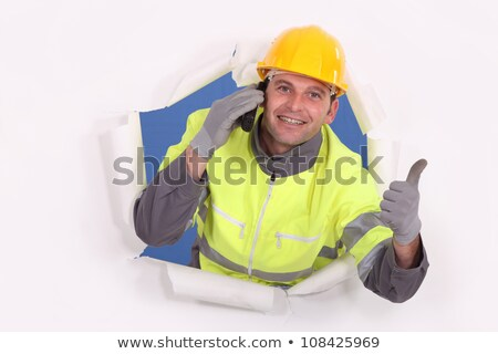 Construction worker breaking through a barrier and giving the thumb's up Stock photo © photography33