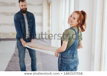 Zdjęcia stock: Woman Carrying Two Planks Of Wood