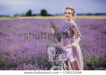 Stock photo: Woman in purple dress and hat with retro bicycle in lavender field