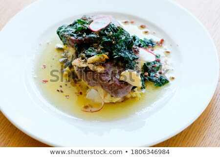 spices, vegetables and a dish of fried medallion Stock photo © OleksandrO