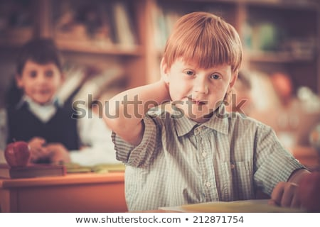 young schoolboy sitting behind a school desk stock photo © paha_l