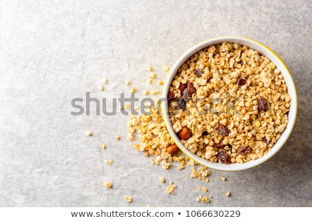 Healthy food: muesli with raisin and nuts on a stone background. Stock photo © mcherevan
