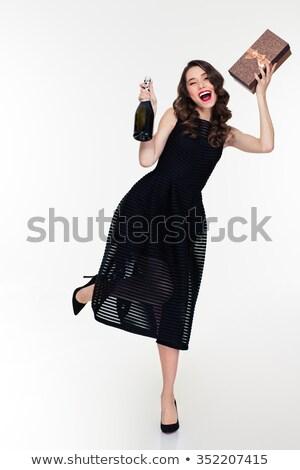 Wesoły młoda kobieta czarna sukienka butelki szampana Zdjęcia stock © deandrobot