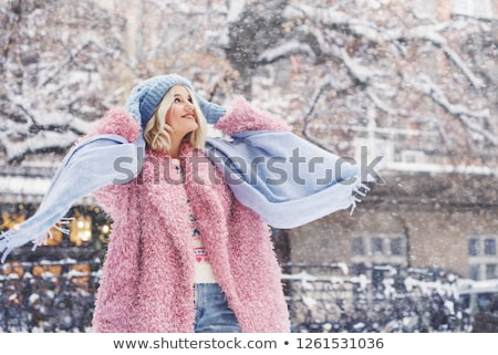 Cute young woman wearing pink coat walking in the street Stock photo © deandrobot