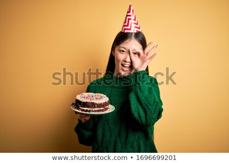 young girl wearing party hat looking at birthday cake smiling stock photo © monkey_business