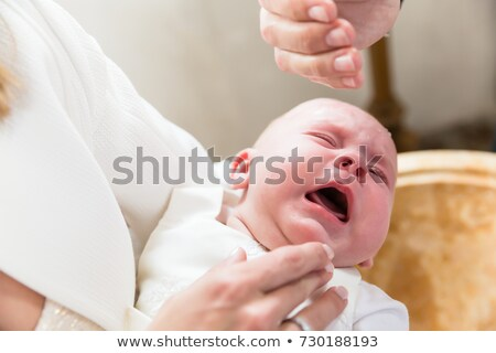 Baby is crying at christening while the priest pours holy water  Stock photo © Kzenon