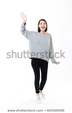 Full length portrait of a girl waving hand to camera Stock photo © deandrobot