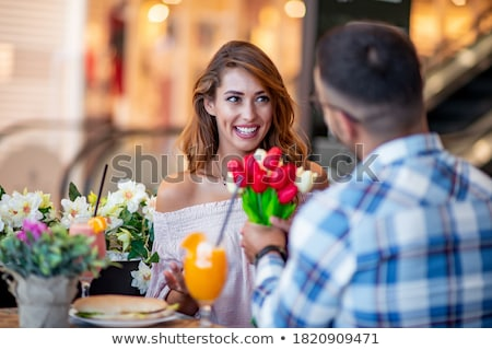 Cheerful woman in cafe drinking juice and eating sandwich. Stock photo © deandrobot