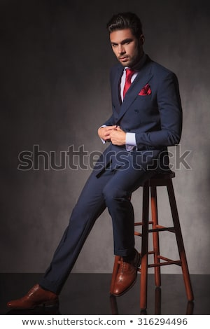 handsome elegant man unbuttoning suit jacket while sitting Stock photo © feedough