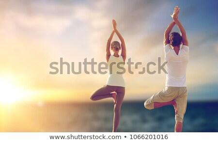 Stock photo: happy couple making yoga and meditating outdoors