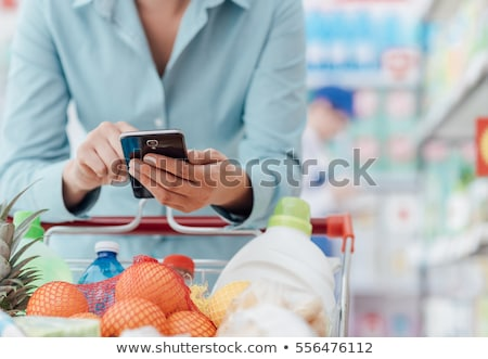 woman with smartphone buying food at supermarket stock photo © dolgachov