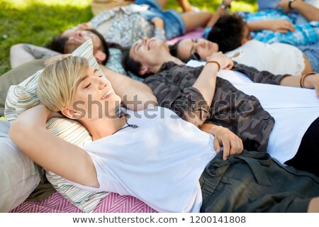 happy friends chilling on picnic blanket at summer Stock photo © dolgachov