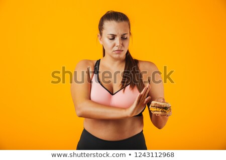 Image of upset chubby woman in tracksuit doing stop gesture whil Stock photo © deandrobot