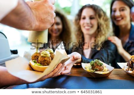 happy friends eating at food truck stock photo © dolgachov
