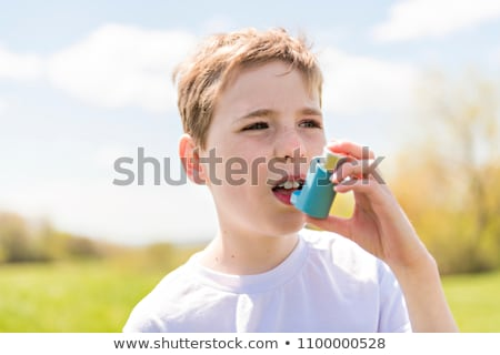 child using inhaler for asthma outside in a park Stock photo © Lopolo