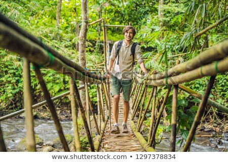 male traveler on the suspension bridge in bali stock photo © galitskaya