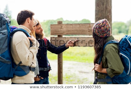 hiking friends with backpacks at signpost Stock photo © dolgachov