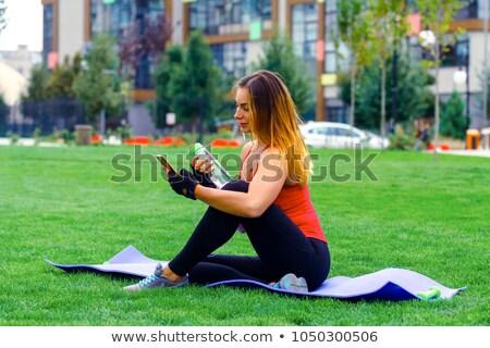 Genç kadın oturma yoga mat içme suyu şişe güzel Stok fotoğraf © boggy