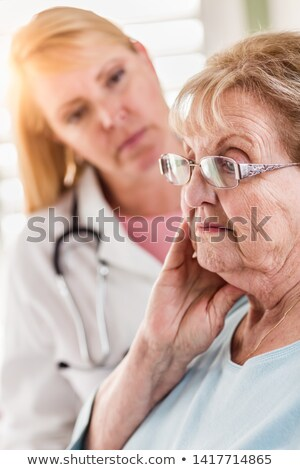 Melancholy Senior Adult Woman Being Consoled by Female Doctor or Stock photo © feverpitch
