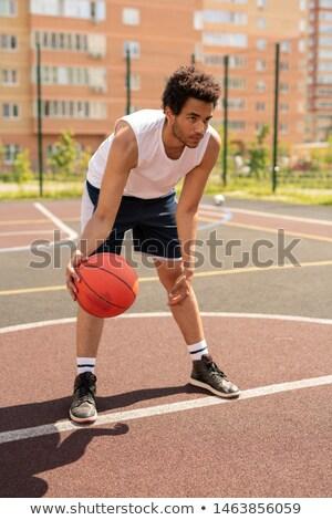 Young basketballer in activewear bending forwards before throwing ball Stock photo © pressmaster
