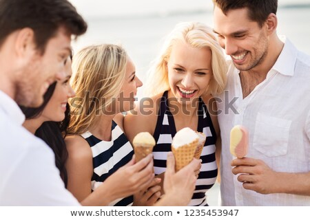 happy friends in striped clothes eating ice cream Stock photo © dolgachov