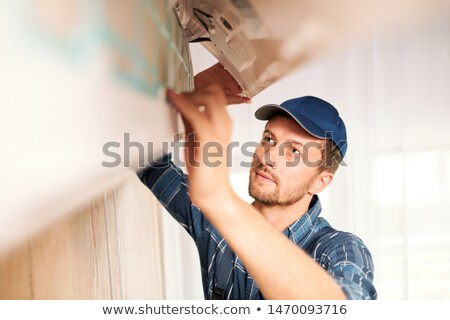 Young workman in workwear trying to find out reason of air conditioner disorder Stock photo © pressmaster