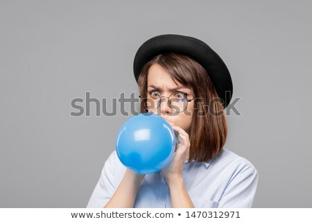 young woman in eyeglasses and hat making effort while blowing blue balloon stock photo © pressmaster