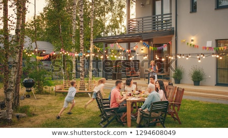 happy family having dinner or summer garden party stock photo © dolgachov