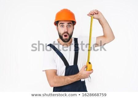 Shocked young man builder holding centimeter. Stock photo © deandrobot