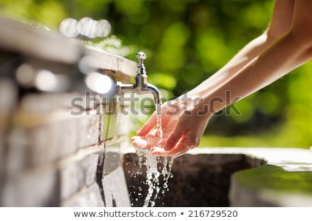 Woman drinking water by a brook Stock photo © photography33
