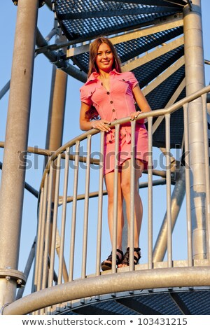 young woman wearing pink dress standing on stairs of lookout tow Stock photo © phbcz