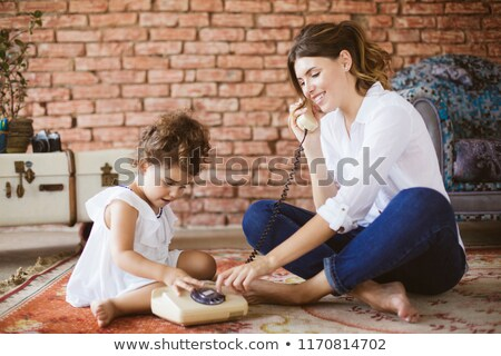 Mother and daughter talking on retro phone. Interior in retro style. Vertical format. Stock photo © Paha_L