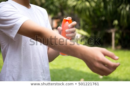 Boy spraying insect repellents on skin Stock photo © galitskaya