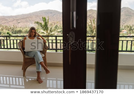 Foto stock: Young woman is working on a laptop on her balcony overlooking the skyscrapers. Freelancer, remote wo